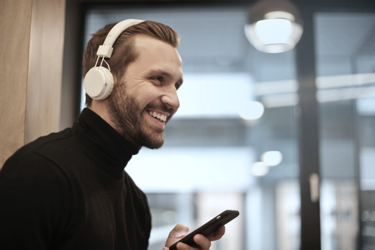 man happily listening to music wearing white headphones inside office | Reasons Why Listening To Peaceful Music Is Good For Your Health peaceful sleep music