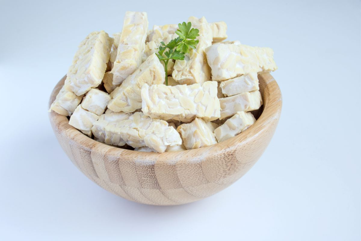 sliced raw tempeh on a wooden bowl | vegan probiotics | probiotics vegan | vegan probiotics whole foods