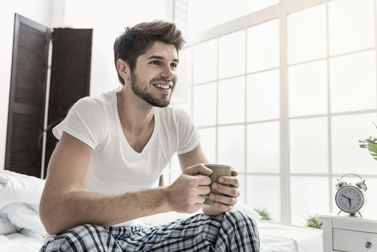 man sitting on the bed drinking a cup of coffee early morning | good habits | good sleeping habits | good daily habits