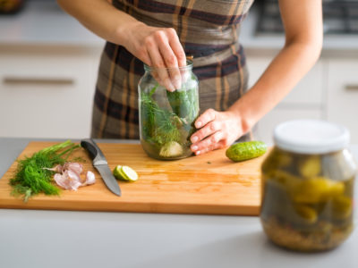 photo of woman filling jars with pickles