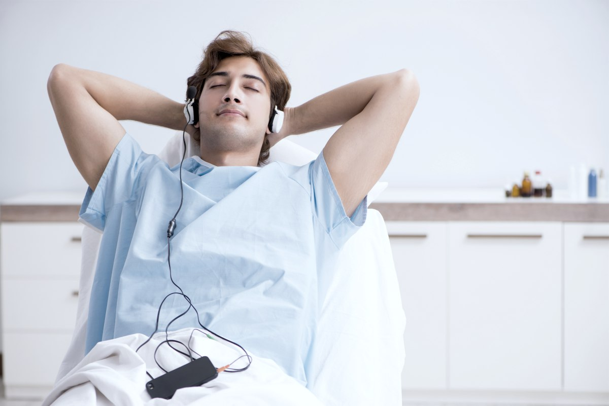 young male patient listening to music while in hospital gown and inside the room relaxing | Reasons Why Listening To Peaceful Music Is Good For Your Health peaceful sleep music