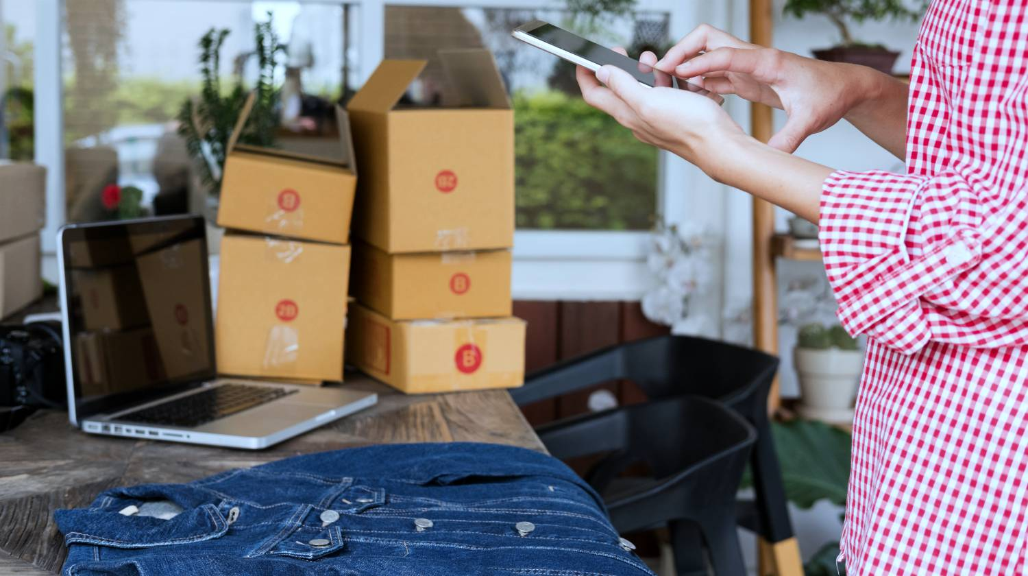 woman selling clothes online taking photo of old jeans | small business owner | grow financial | sustainable income | sustainable money making | Featured