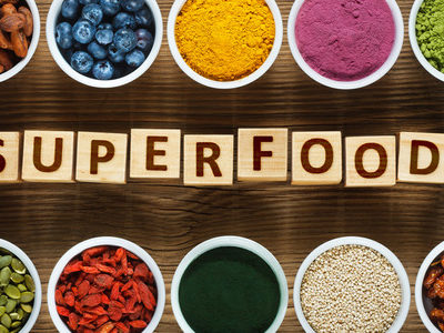 """various foods in bowls with """"superfood"""" spelled using blocks"""