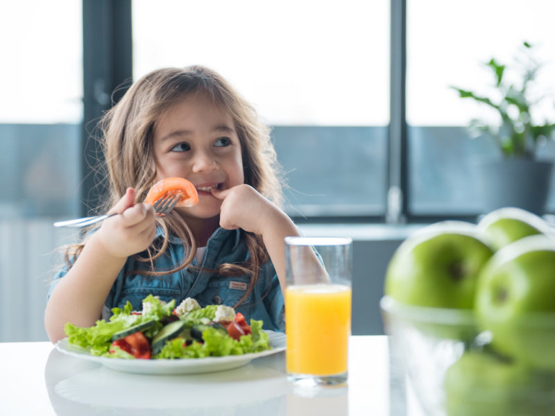 photo of a young girl eating salad and drinking juice
