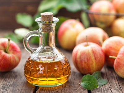 photo of apple cider vinegar and apples on table