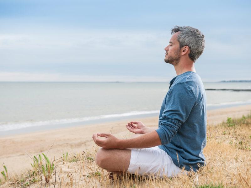 photo of man practicing mindfulness meditation on a beach
