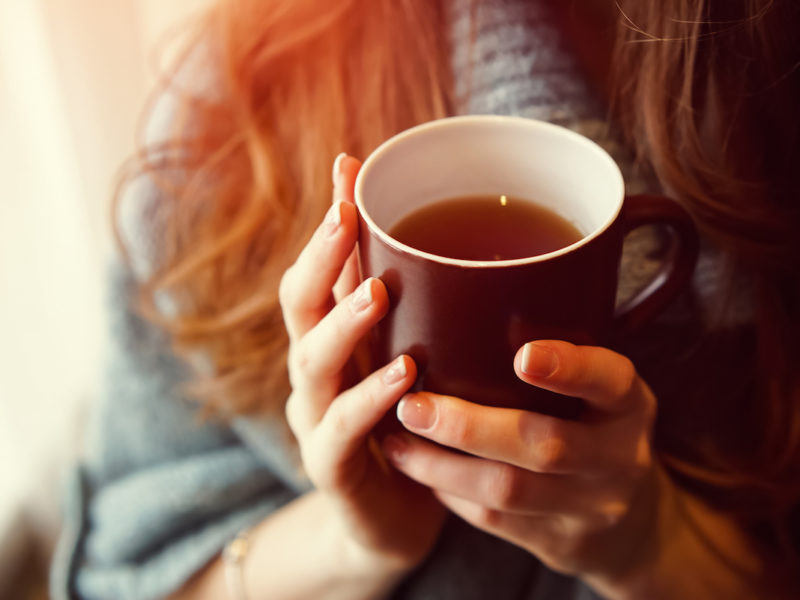 photo of woman holding cup of tea