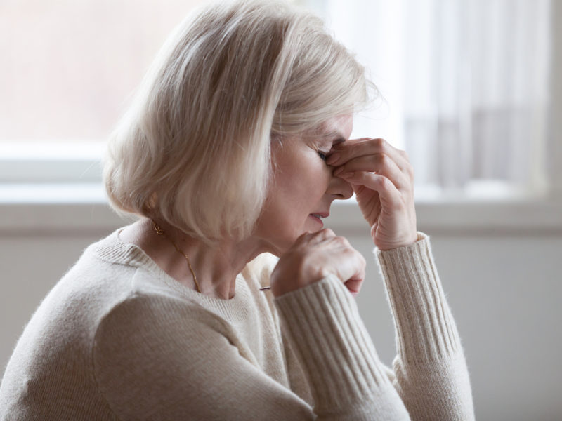 Fatigued, upset older woman massaging nose bridge feeling eye strain or headache trying to relieve pain
