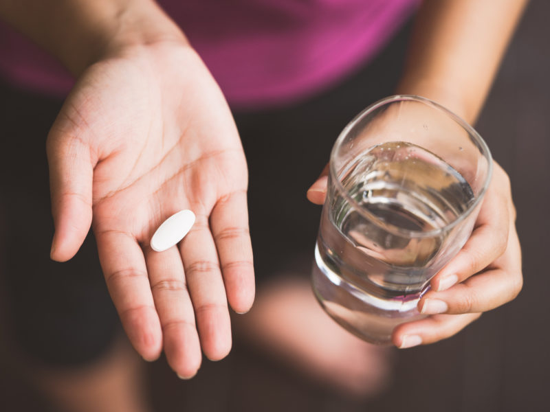 photo of woman holding pill in one hand and glass of water in other, representing vitamin K2-7 supplement