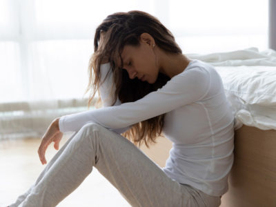 Unhappy woman touching hair, sitting on floor at home, thinking about problems, upset girl feeling lonely and sad, psychological and mental troubles